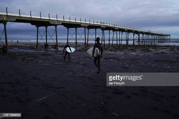 Surfers walk across sea coal deposited on Saltburn beach as they head for a surf on November 24 2020 in Saltburn By The Sea England Sea coal washes...