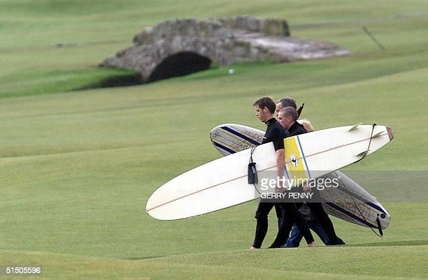 Surfers walk across St Andrews Old Course in front of the famous Swilken Bridge 12 October 2000 after a days surfing in St Andrews Bay during the...
