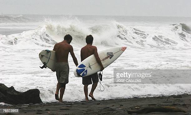 Surfers walk along El Tunco beach close to El Puerto de La Libertad 31 km from San Salvador 05 September 2007 Felix wich is degradated to a tropical...