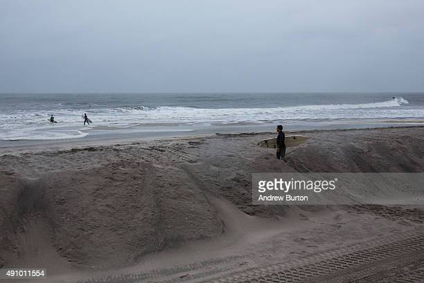 Surfers walk along the beach observing the swells during the potential build up to Hurricane Joaquin on October 2 2015 in Long Beach New York The...