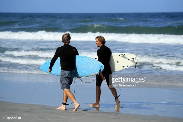Surfers walk down the beach on April 17 2020 in Jacksonville Beach Florida Jacksonville Mayor Lenny Curry announced Thursday that Duval County's...