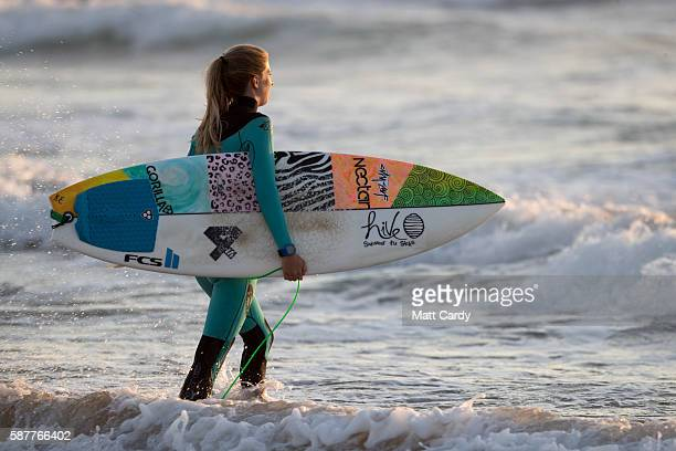 Surfers walk into the sea as the sun sets at Fistral Beach in Newquay on August 9 2016 in Cornwall England From tomorrow the Cornish seaside town...