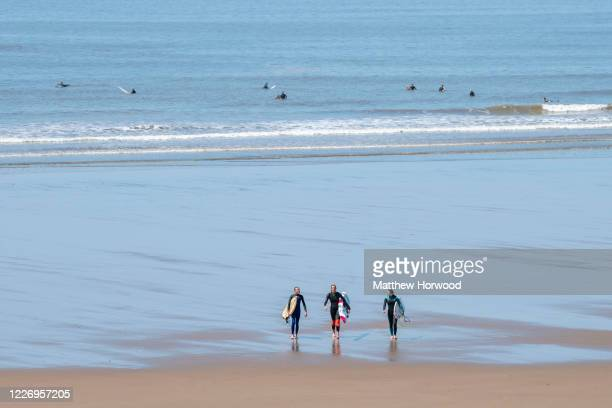 Surfers walk on a quiet Rest Bay beach on May 25, 2020 in Porthcawl, United Kingdom. The British government has started easing the lockdown it...