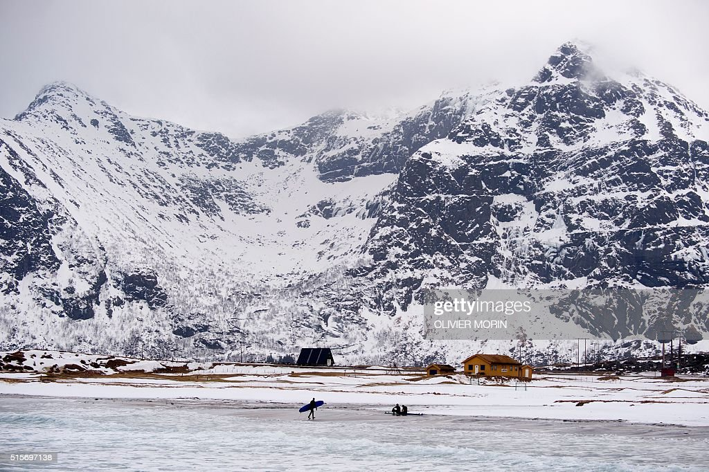 Surfers walk on the snow covered beach of Flakstad, near Rambeg, as they have a break during a surf session on the Lofoten Island, Arctic Circle, on March 12, 2016. Surfers from all over the world come to Lofoten island to surf in extrem conditions. Ocean temperature is 5-6 °C, air temperature around 0°C in spite of a weather very unstable. / AFP / OLIVIER