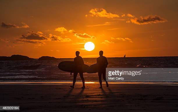 Surfers walk out of the sea as the sun sets at Porthmeor Beach in St Ives on July 29 2015 in Cornwall England After a unsettled start to the school...