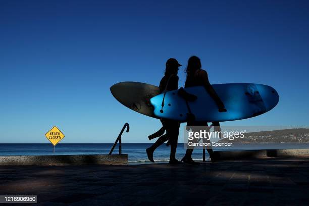 Surfers walk past a Beach Closed sign at Manly Beach on April 05 2020 in Sydney Australia Northern Beaches Council today closed Manly North Steyne...