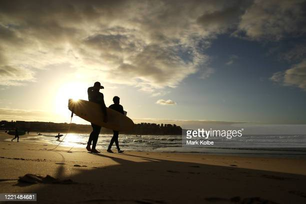 Surfers walk to the ocean after the 7am reopening of Bondi beach on April 28 2020 in Sydney Australia Waverley Council reopened Bondi Bronte and...