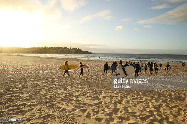 Surfers walk to the water through a designated walkway at Bondi beach after the 7am reopening on April 28 2020 in Sydney Australia Waverley Council...