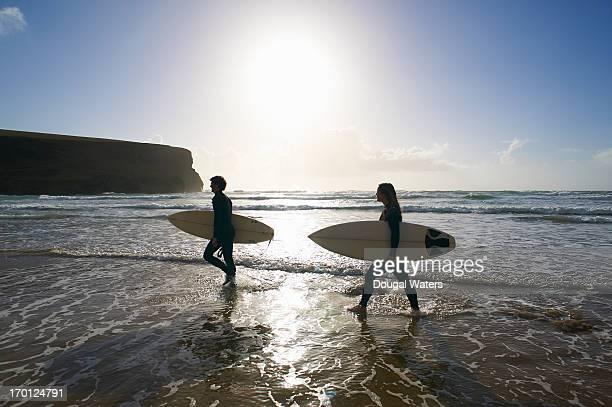 Surfers walking along beach.