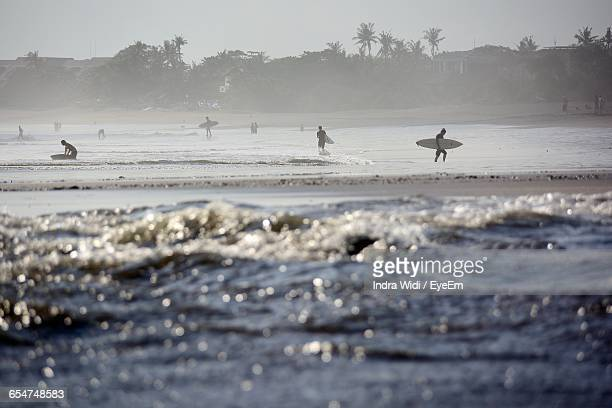 Surfers Walking At Beach