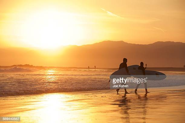 Surfers walking on the shoreline during sunset in Venice beach California June 2015