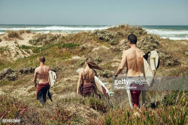 3 surfers walking through sand dunes with boards - branding stockfoto's en -beelden