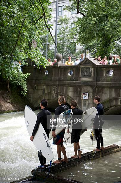 Surfers watch the action on the Eisbach a man made river using the Isar River as it's source of water which flows through the Englischer Garten on...