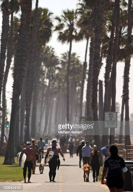 Surfers wearing face masks walk down a path at the beach on April 22 2020 in Huntington Beach California Southern California is expecting summer like...