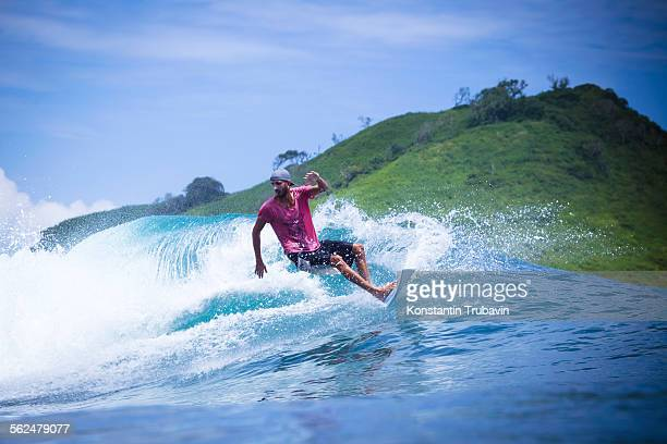 Surfing a wave in Lombok island, Indonesia.