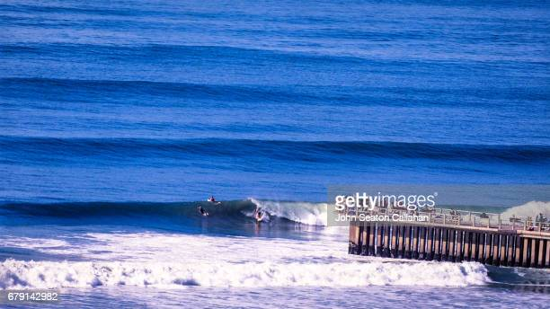 surfing at the new pier - durban beach stock photos and pictures