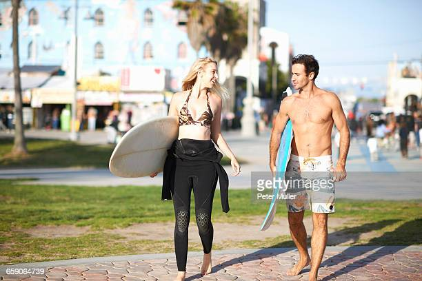 Surfing couple carrying surfboards at Venice Beach, California, USA