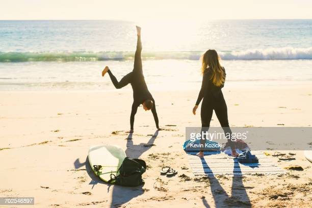 surfing couple cartwheeling on newport beach, california, usa - newport ca stock pictures, royalty-free photos & images