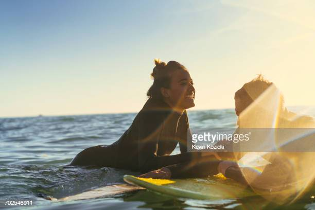 surfing couple leaning on surfboards in sea, newport beach, california, usa - newport ca stock pictures, royalty-free photos & images