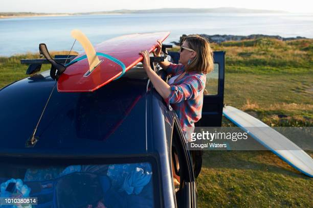 surfing couple on road trip removing surfboards from roof rack. - dougal waters stock pictures, royalty-free photos & images