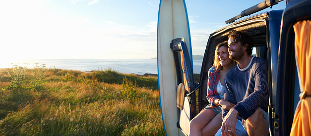 Surfing couple sitting in camper van on idyllic Atlantic coastline. - gettyimageskorea