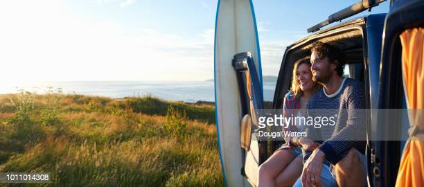 surfing couple sitting in camper van on idyllic atlantic coastline. - buitensport stockfoto's en -beelden