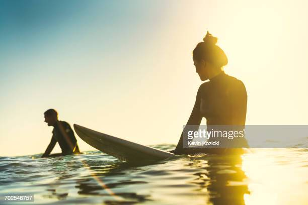 surfing couple wading in sea, newport beach, california, usa - newport ca stock pictures, royalty-free photos & images