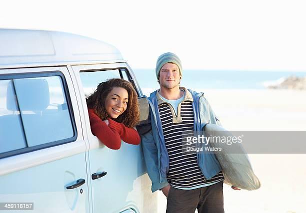 Surfing couple with camper van beside beach.