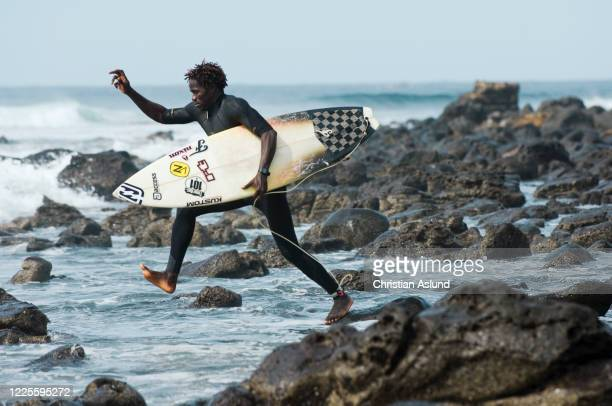 surfing in africa, a surfer heading out to the waves outside n'gor in dakar, senegal - dakar photos et images de collection