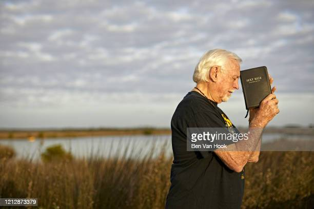 Portrait of former surfing champion Jack Roland Murphy holding the Bible during photo shoot at Fort Island Trail Beach. Murphy has been convicted of...