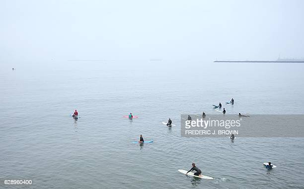 Surfing Santa Michael Pless and fellow surfers wait for waves on a hazy morning at Seal Beach California on December 10 where Pless runs a surfing...