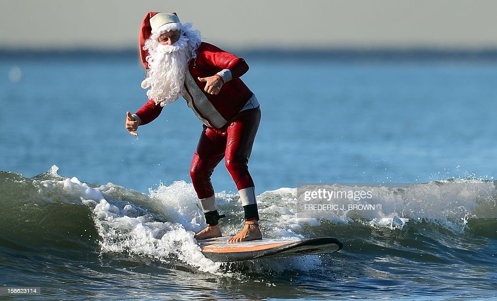 Surfing Santa, Michael Pless, 62, gives a 'hang-ten' gesture while riding a wave off Seal Beach, south of Los Angeles, on December 21, 2012. Pless, who also runs a surfing school, has been dressing up as Santa Claus and taking to the waves in costume since the 1990's, sometimes joined by his wife Jill in a Mrs. Claus outfit. AFP PHOTO / Frederic J. BROWN