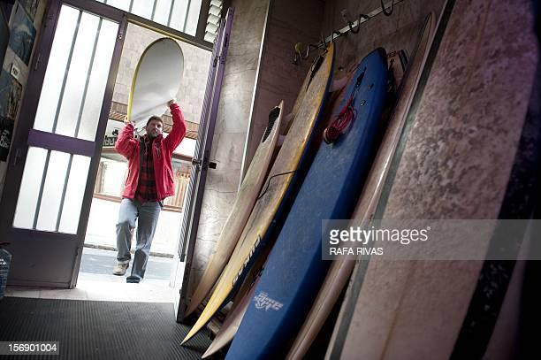 Surfing teacher Mike Dobos carries a board in his Surfin' Mundaka school on November 21 2012 in the northern Spanish Basque village of Mundaka Rather...