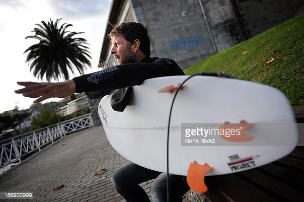 Surfing teacher Mike Dobos gestures as he sits with his board on November 21 2012 in the northern Spanish Basque village of Mundaka Rather than mope...