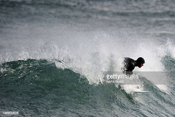 Surfing teacher Mike Dobos glides on a wave on November 21 2012 in the northern Spanish Basque village of Mundaka Rather than mope around at home...