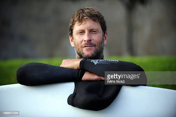 Surfing teacher Mike Dobos poses with his board on November 21 2012 in the northern Spanish Basque village of Mundaka Rather than mope around at home...