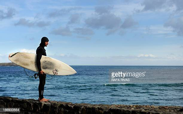 Surfing teacher Mike Dobos stands on the seashore before getting into the water on November 21 2012 in the northern Spanish Basque village of Mundaka...