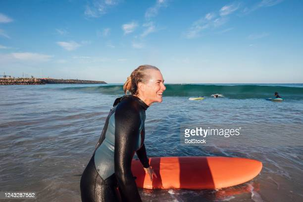 surfing tutor smiling - sea swimming stock pictures, royalty-free photos & images