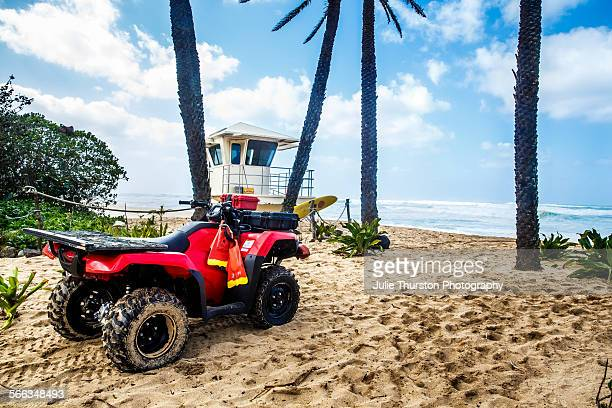 Surfs up by a lifeguard shack red ATV beach buggy and fins and yellow rescue surfboard on a white sandy palm tree lined beach under blue skies at the...
