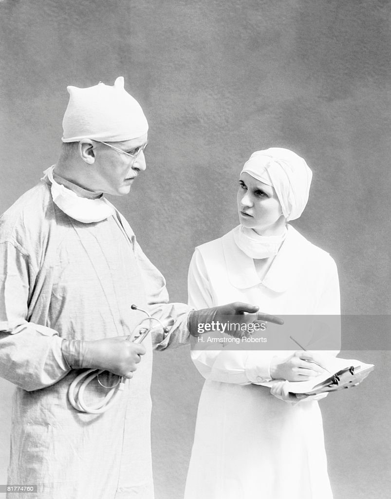 Surgeon And Nurse In Surgical Gowns Nurse Writing In Chart Doctor ...