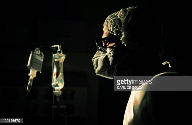 Surgeon checks the intravenous drip of one of his COVID-19 patients, at the Oceanico hospital in Niteroi, Rio de Janeiro on June 22 during the...