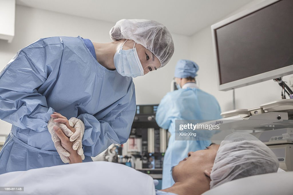 Surgeon consulting a patient, holding hands, getting ready for surgery : Stock Photo
