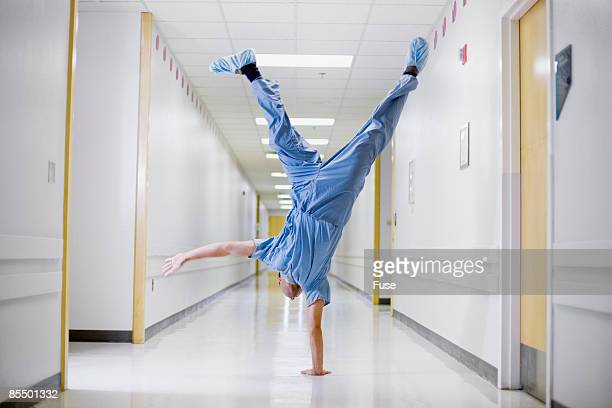surgeon doing cartwheel in hallway - acrobatic activity stock photos and pictures