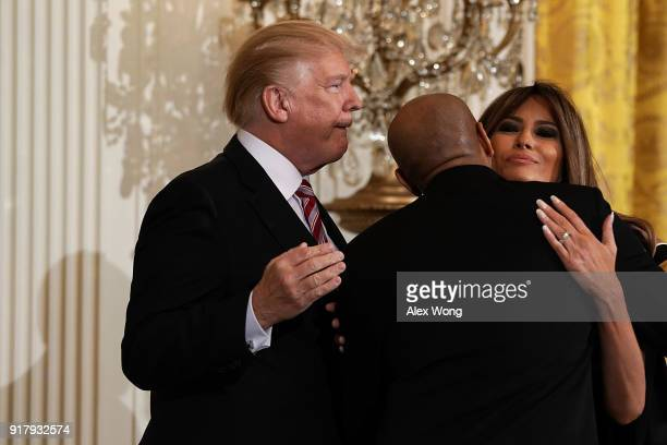 S Surgeon General Jerome Adams hugs first lady Melania Trump as President Donald Trump looks on during a reception in the East Room of the White...