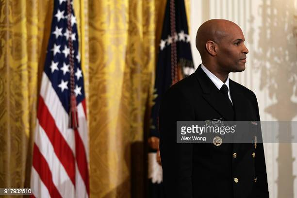 S Surgeon General Jerome Adams listens during a reception in the East Room of the White House February 13 2018 in Washington DC President Donald...
