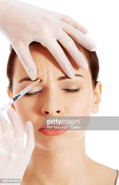 surgeon giving botox injection on woman forehead against white background - botox stock pictures, royalty-free photos & images