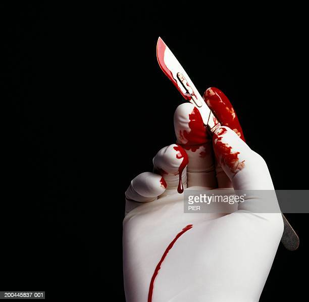 surgeon holding blood stained scalpel, close-up of hand - scalpel stock photos and pictures