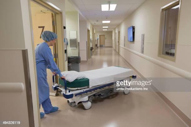 Surgeon pushing gurney in hospital corridor