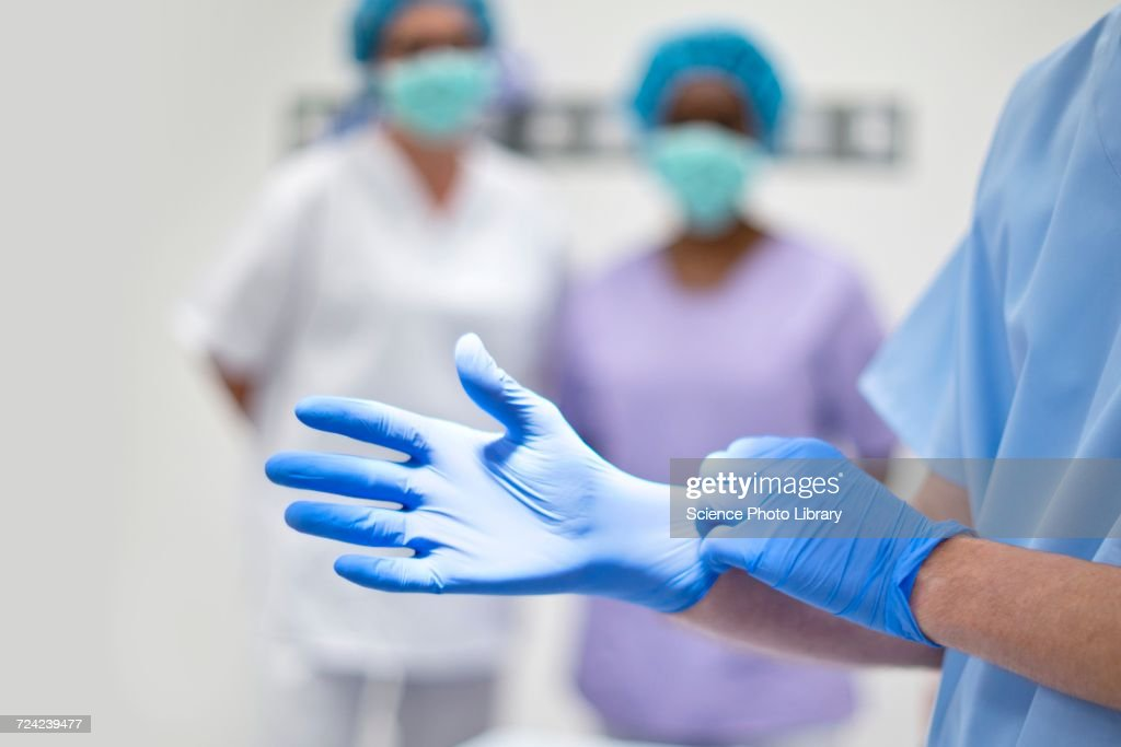 Surgeon putting on latex glove : Stock Photo