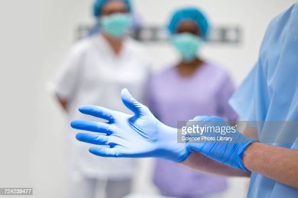 Surgeon putting on latex glove